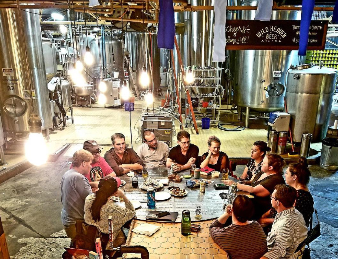 A group of people sit around a table. There are glasses of beer and plates on the table. Surrounding the table is the interior of a brewery with kegs and industrial brewing components.