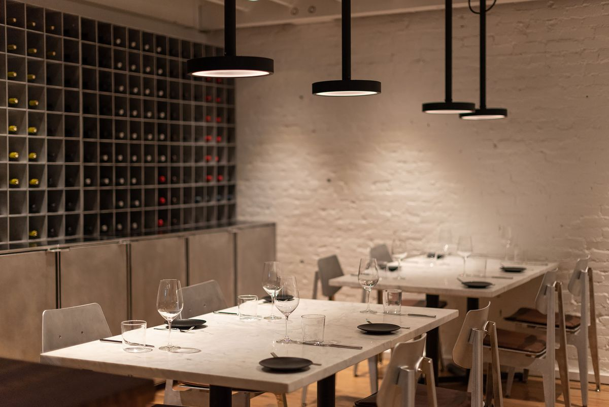 A white marble table under low lighting, backed by a wall of wine.