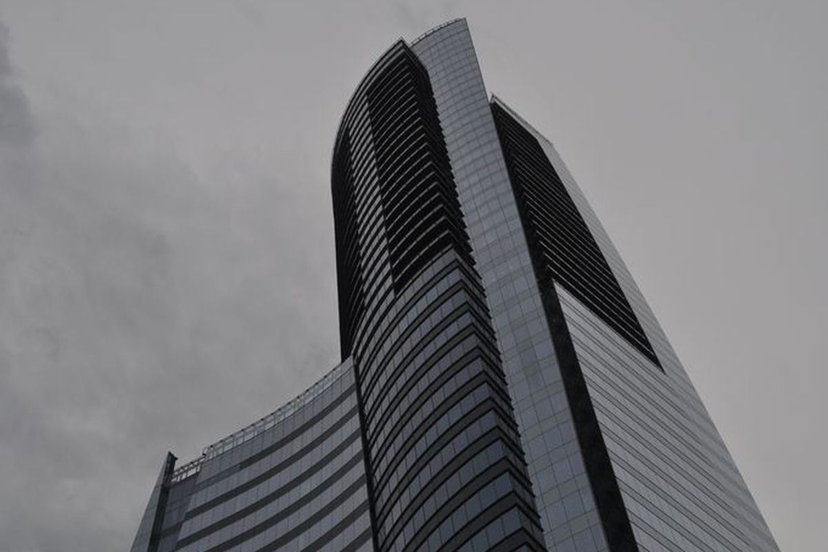A towering, sweeping blue glass building against a grey sky.