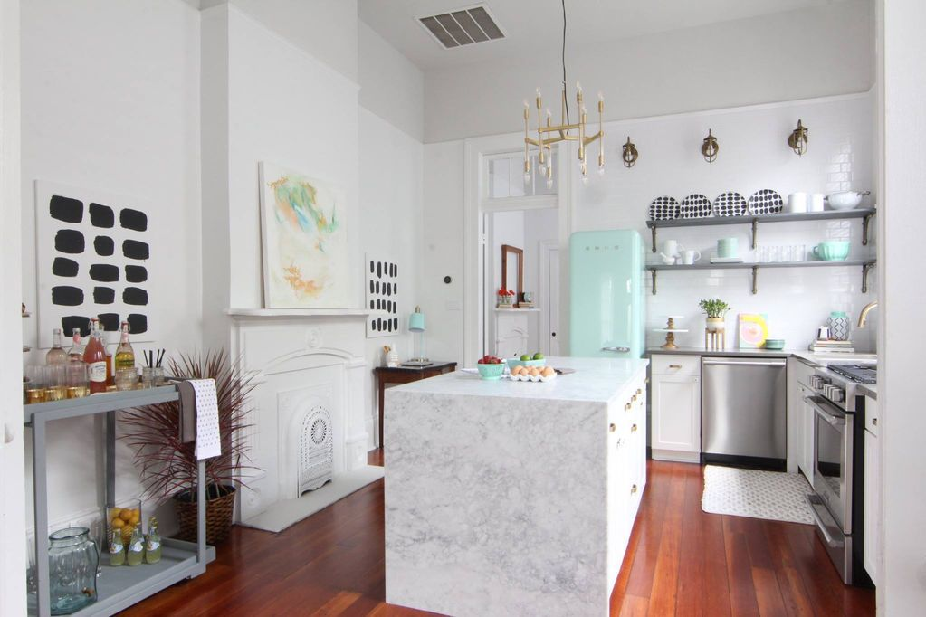 Stylish kitchen with white subway tile and a waterfall counter island, plus a white fireplace