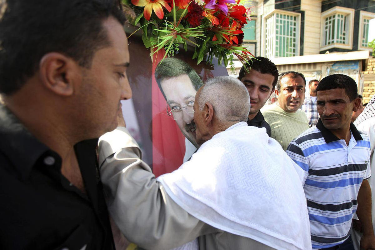 A relative of former Basra governor, Mohammed al-Wailie, kisses his poster during his funeral in Basra, 340 miles (547 kilometers) southeast of Baghdad, Iraq, Friday, Sept. 28, 2012. Gunmen shot dead the former governor, Mohammed al-Wailie, as he was driv