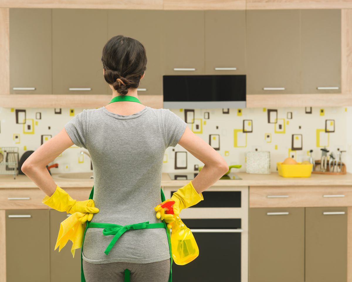 Back view of woman in kitchen wearing rubber gloves and holding cleaning supplies.