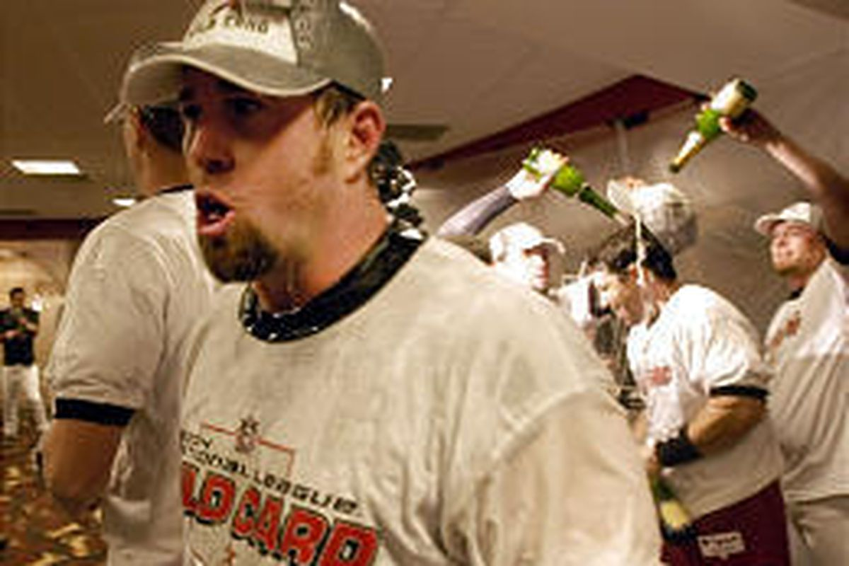 Houston Astros' Jeff Bagwell, left, yells as Brad Ausmus is doused in champagne after the Astros clinched the National League wild-card spot.