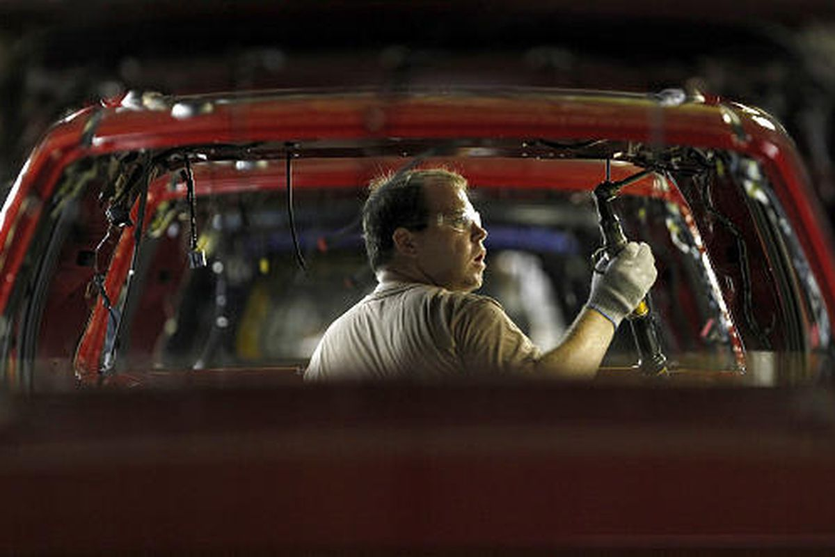 Alex Stigall, of Richmond, Mo., installs side airbags in a 2010 Ford Escape at Ford's Kansas City assembly plant Wednesday in Claycomo, Mo. Ford was one of the top gainers from the Cash for Clunkers program.