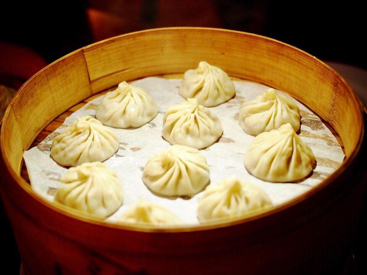 A wooden bowl containing 10 soup dumplings