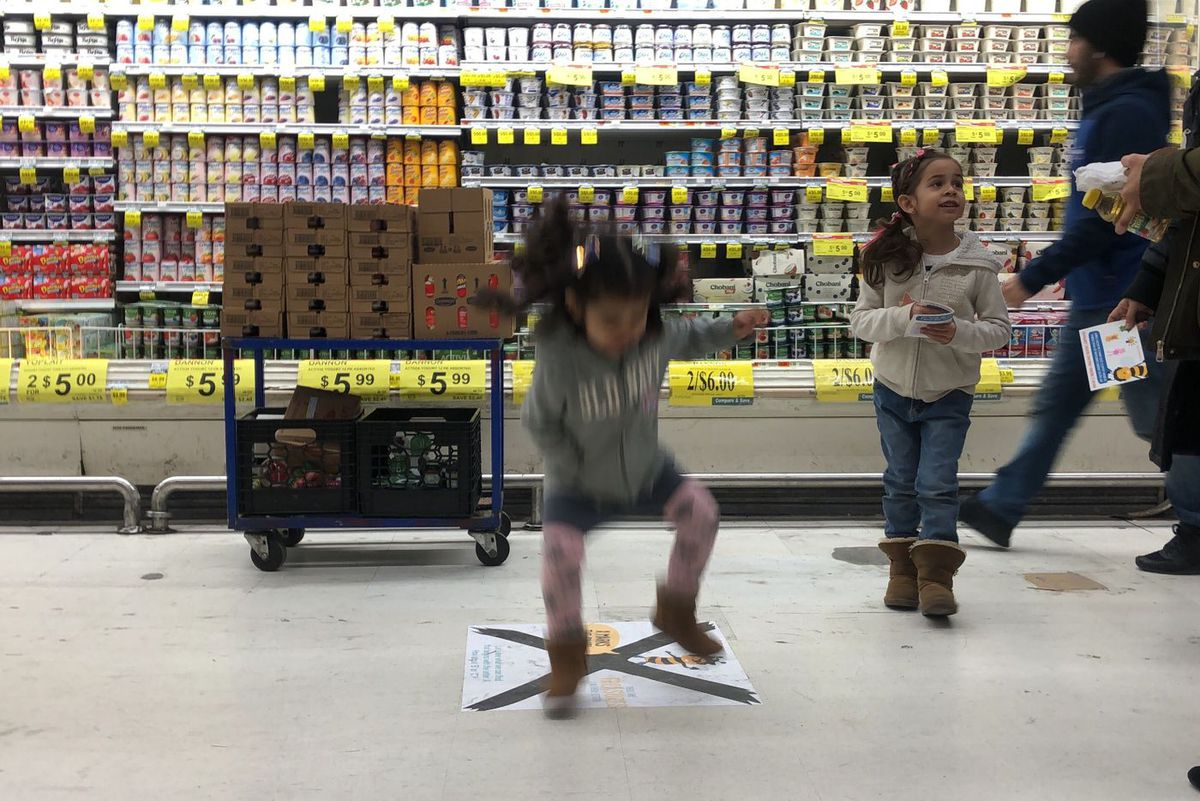 Cailynn, 3, jumps on a sign in the Learning Landscapes scavenger hunt at Food Bazaar in Brownsville, Jan. 30, 2020.