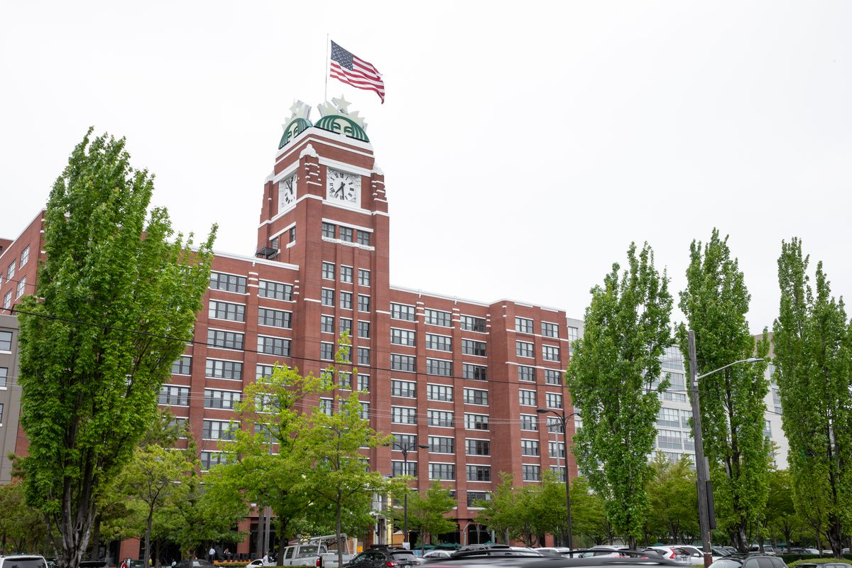 A view of the brick Starbucks HQ building in Seattle, with an American flag flying on top, surrounded by trees