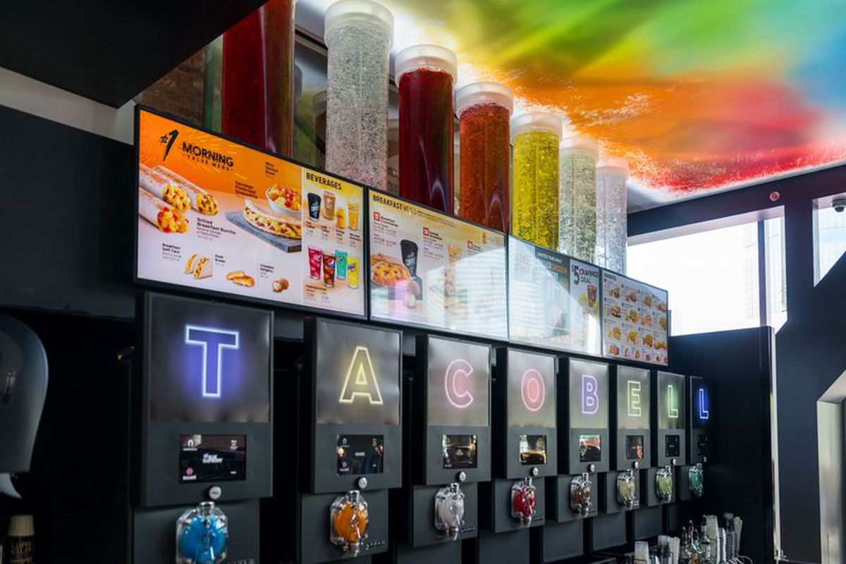 A row of Twisted Freeze machines at a Taco Bell Cantina, featuring brightly colored liquids and neon accents