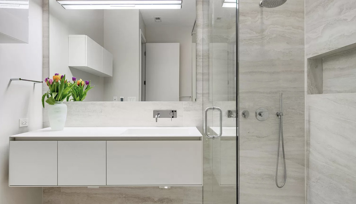 The bathroom has a floating vanity, a walk-in glass shower, and a soaking tub.