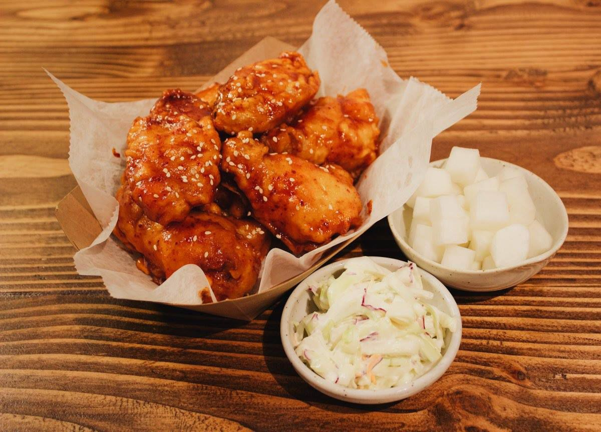 Saucy fried chicken sits in a disposable container with sides of radish and slaw next to it on a wooden table