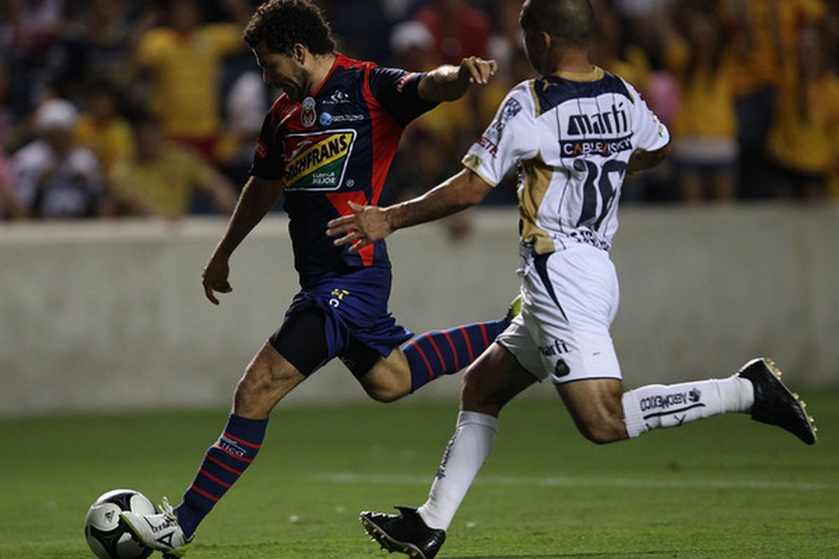 BRIDGEVIEW IL - JULY 17: Miguel Sabah #9 of Monarcas Morelia moves to shoot past Fernando Espinosa #16 of Pumas UNAM during a SuperLiga 2010 match at Toyota Park on July 17 2010 in Bridgeview Illinois. (Photo by Jonathan Daniel/Getty Images)