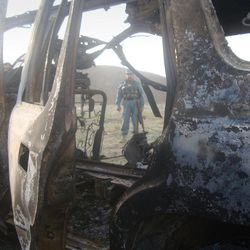An Afghan policeman is seen through a door of burnt vehicle after a gun battle in Pul-e- Alam, Logar province of Afghanistan, Monday, April 16, 2012. The eastern cities of Jalalabad, Gardez and Pul-e-Alam also came under attack, with suicide bombers trying to storm a NATO base, an airport and police installations.