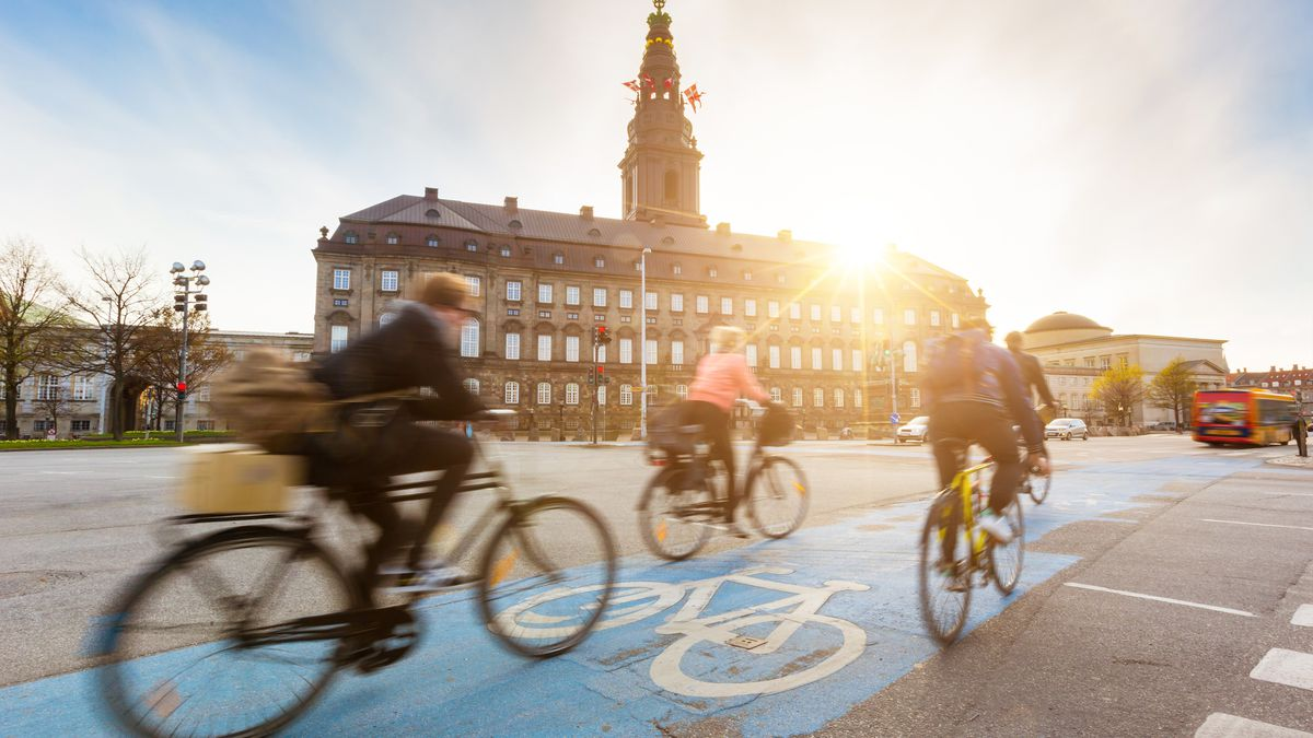 A trio of cyclists riding down a bike lane in front of a landmark building.