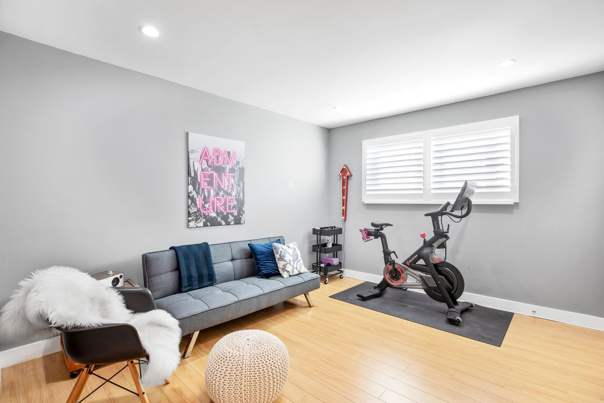 A room with a sofa and chair, plus a stationary bike and weights.