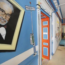 In this May 4, 2017, photo a mural that features Theodor Seuss Geisel, left, also know by his pen name Dr. Seuss, rests on a wall near an entrance at The Amazing World of Dr. Seuss Museum, in Springfield, Mass. The new museum devoted to Dr. Seuss opened on June 3 in his hometown.