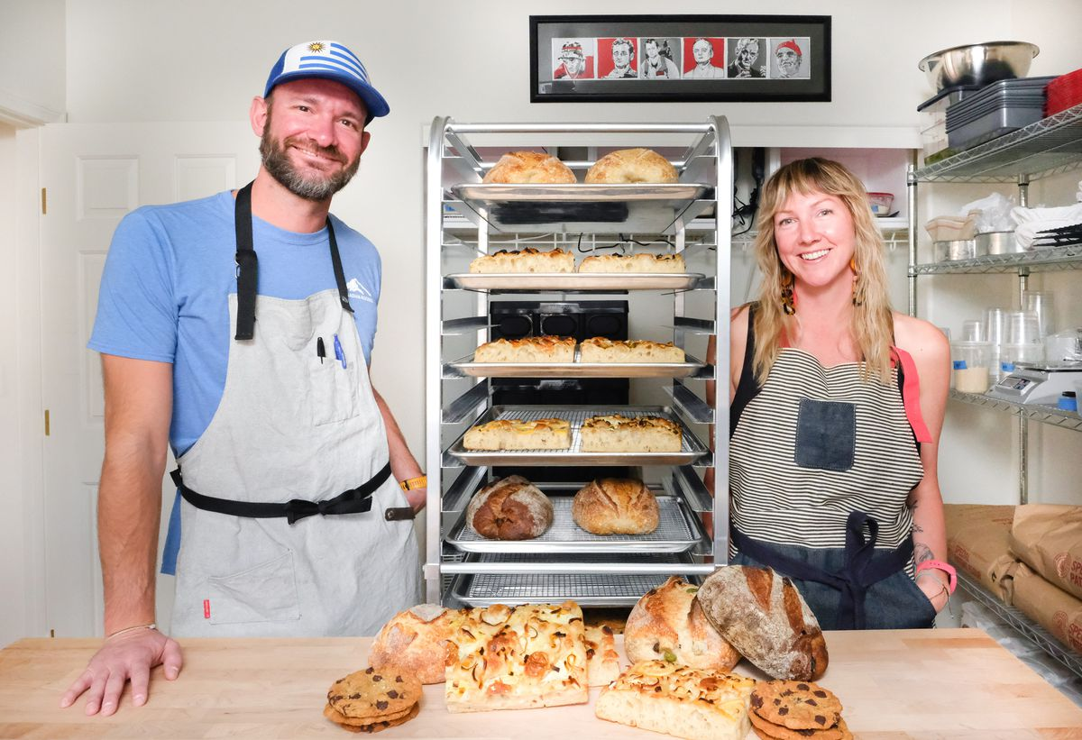 A man and a woman stand on either side of a bakery rack