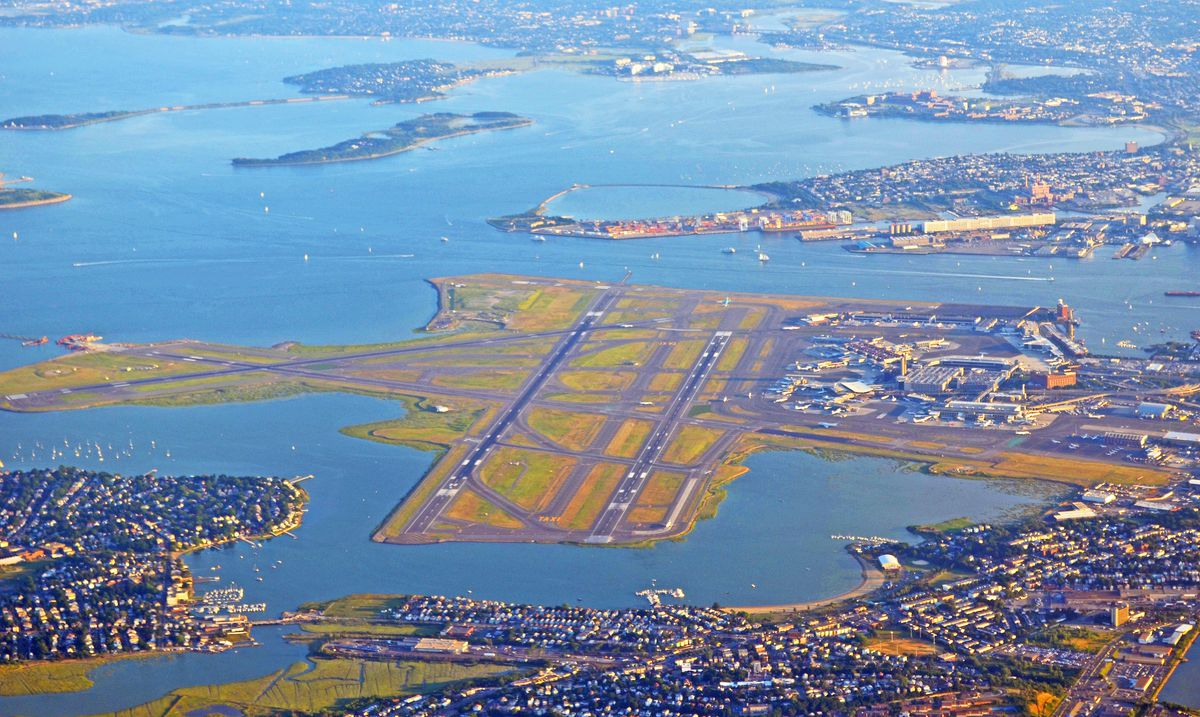 An aerial shot of runways at an airport with a city and water surrounding the runways.