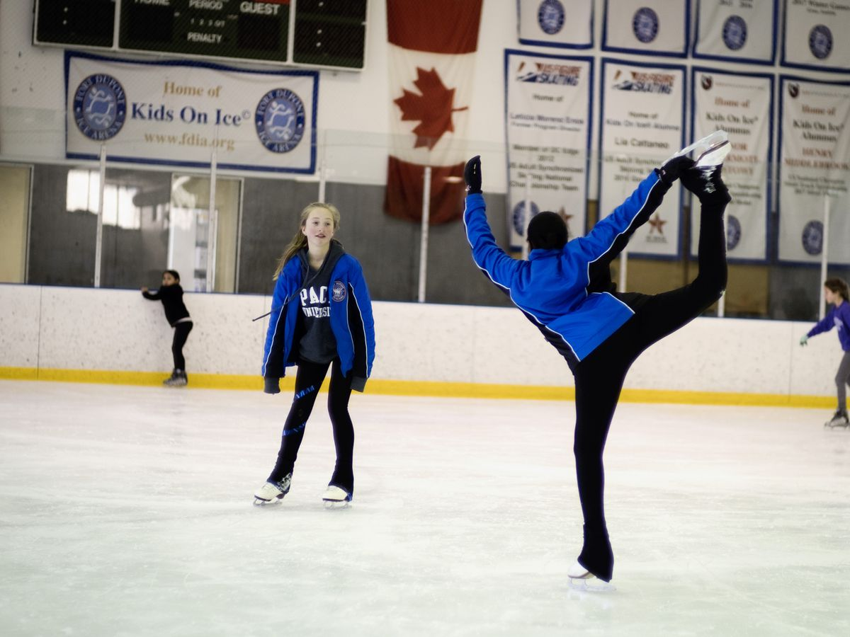 Two young girls skate at an ice skating rink. One holds her leg up above her head.