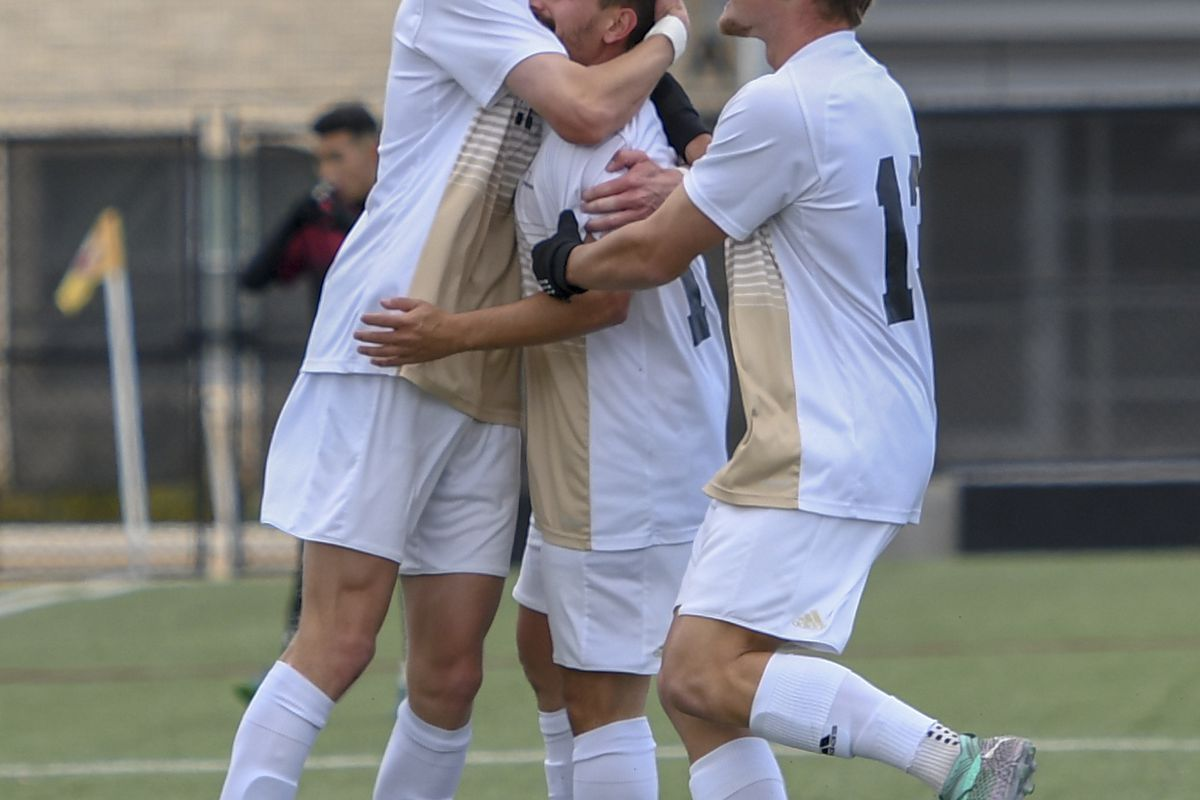 Two teammates celebrate with Amit Hefer (center) after a goal.