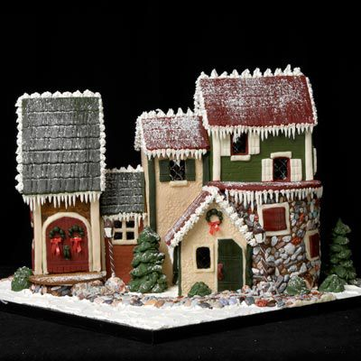Classic gingerbread house with three green, cream, and maroon used to color the exterior.