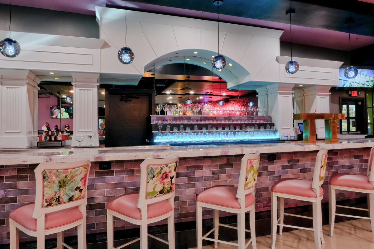 A bar with floral chairs and a pink barback