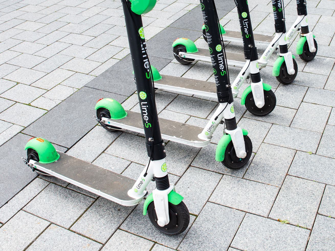 A row of green, white, and black lime electric scooters lined up side by side on a sidewalk of rectangular pavers.