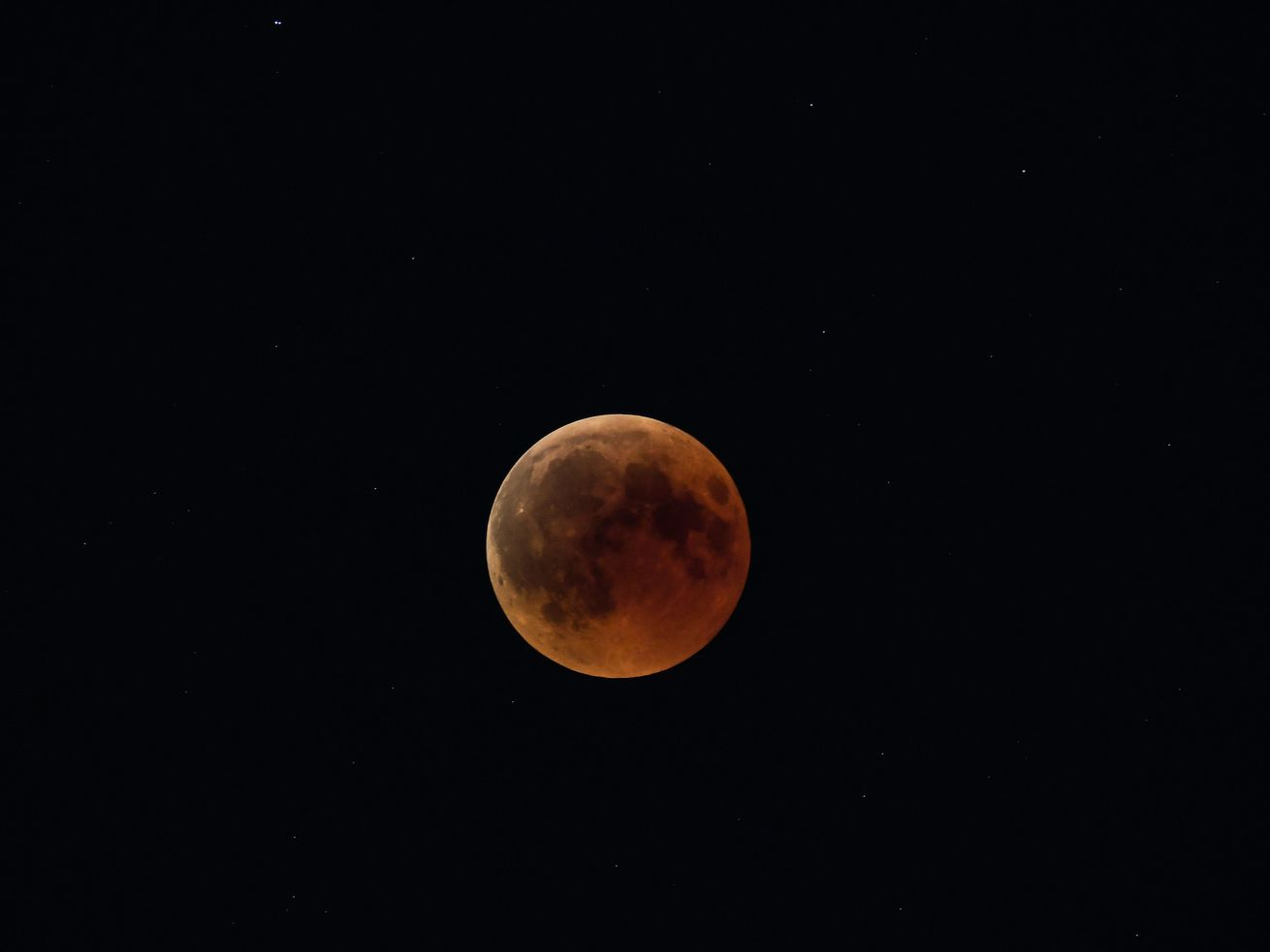 "A picture shows the full moon during a ""blood moon"" eclipse as seen from Athens on July 27, 2018"