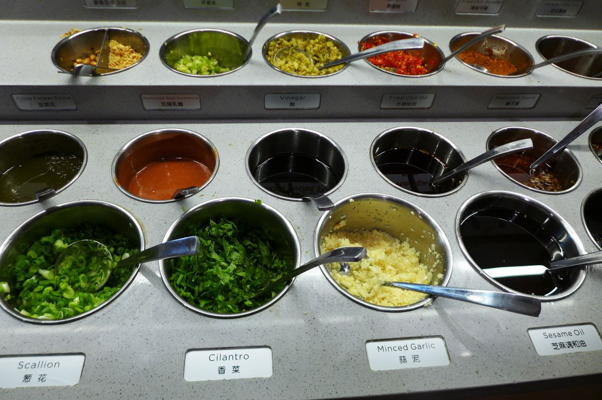 A counter holds many recessed tubs containing herbs, crushed garlic, and sauces...