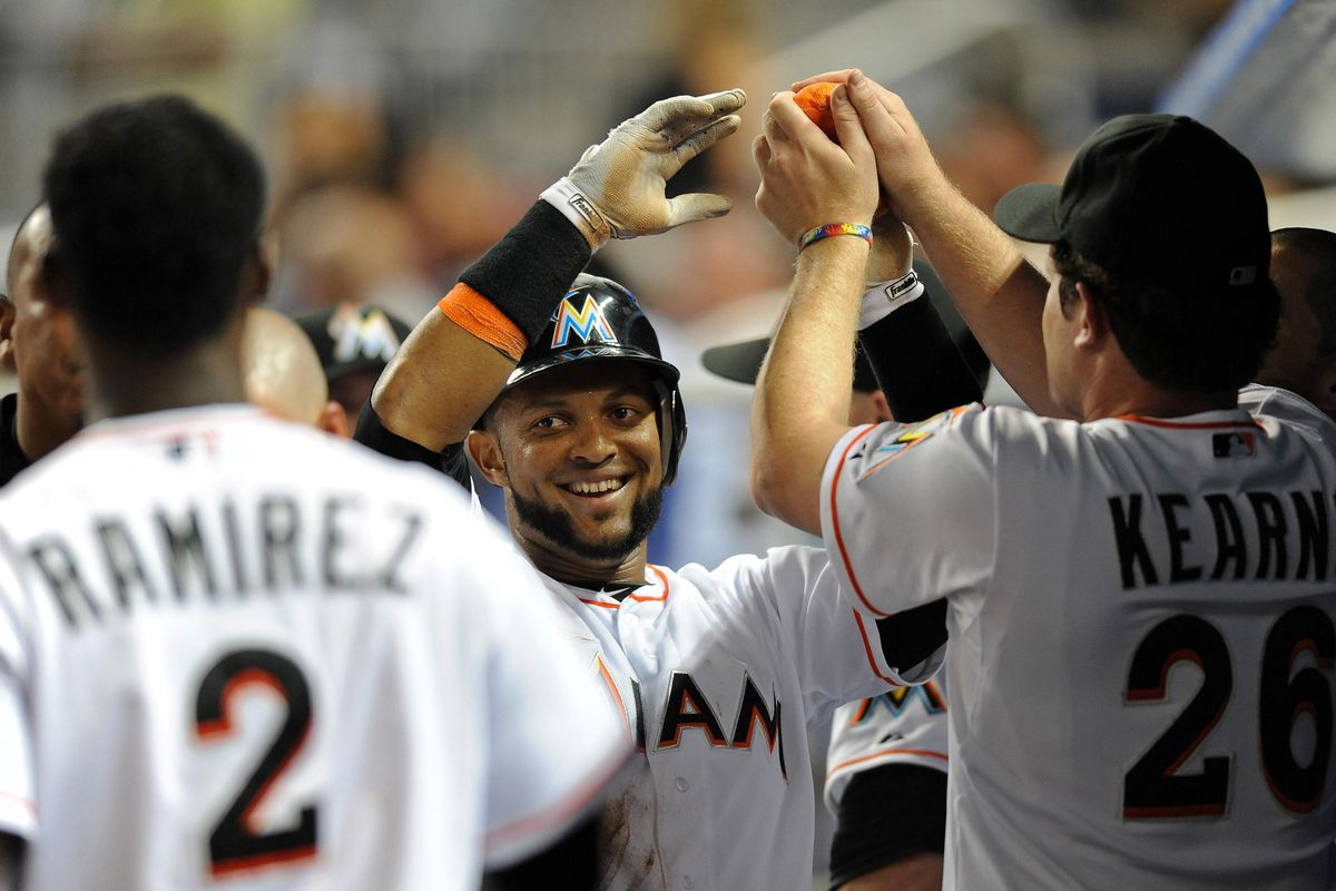 July 14, 2012; Miami, FL, USA; Miami Marlins center fielder Emilio Bonifacio (center) is greeted by teammates after scoring a run during the fifth inning against the Washington Nationals at Marlins Park. Mandatory Credit: Steve Mitchell-US PRESSWIRE