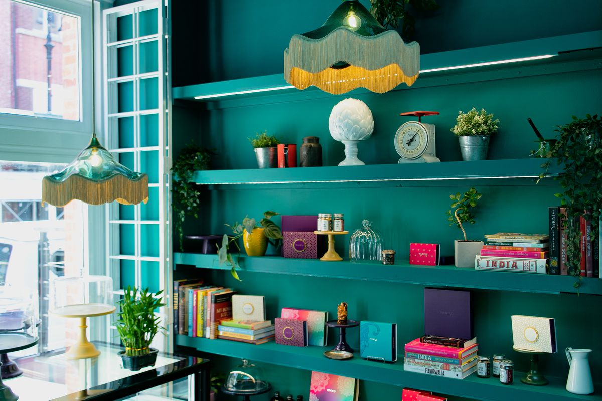 Colorful books, jars, and knickknacks are set on teal shelving against a teal wall near a window at the front of the shop.