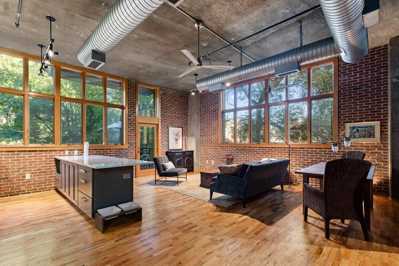 A huge living room space with brick walls and a balcony.