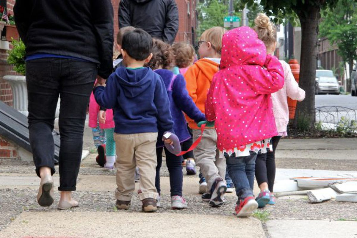 A group of small children are led by a caregiver down a Philadelphia street.