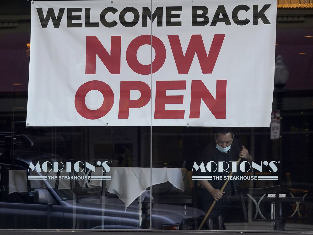 """In this March 4, 2021, file photo, a sign reading """"Welcome Back Now Open"""" is posted on the window of a Morton's Steakhouse restaurant as a man works inside during the coronavirus pandemic in San Francisco. California added 141,000 jobs in February as more than a quarter of a million people returned to the workforce. The California Employment Development Department said Friday, March 26, that the state's unemployment rate in February was 8.5%, down from 9% in January."""