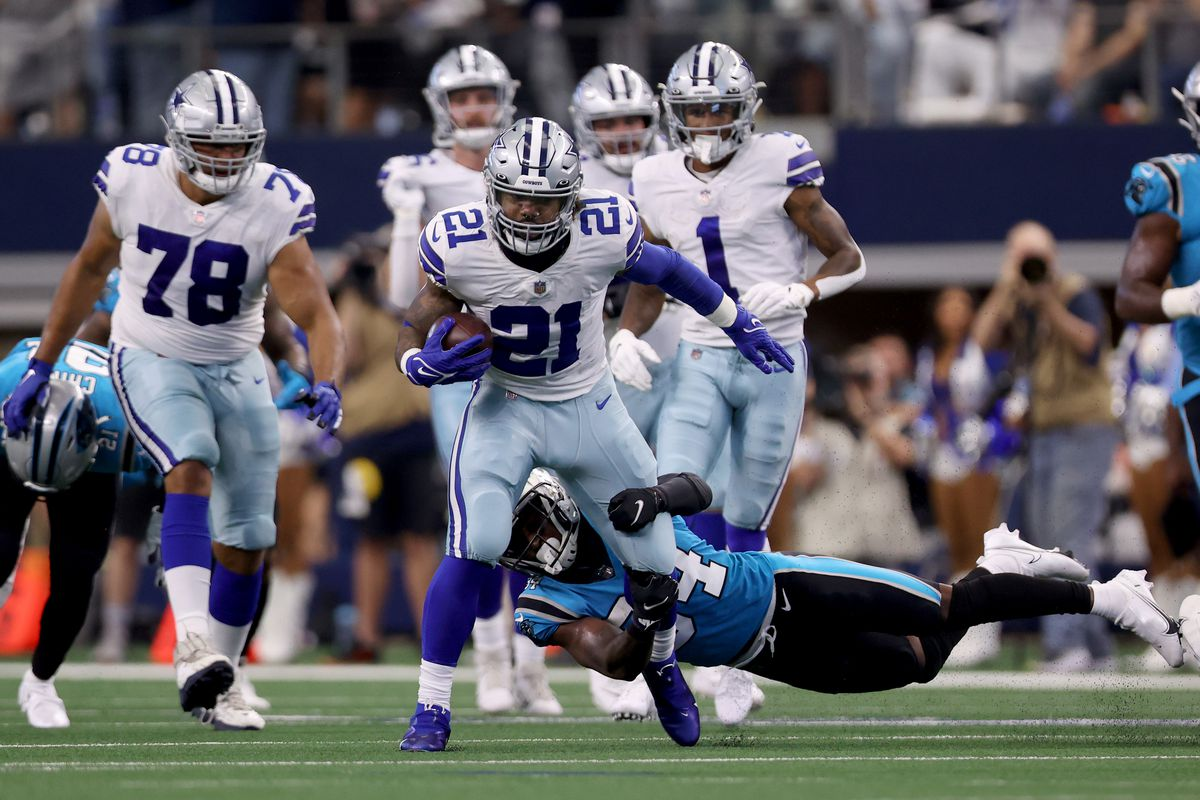 Running back Ezekiel Elliott #21 of the Dallas Cowboys carries the ball against defensive back Sean Chandler #34 of the Carolina Panthers in the first half at AT&T Stadium on October 03, 2021 in Arlington, Texas.
