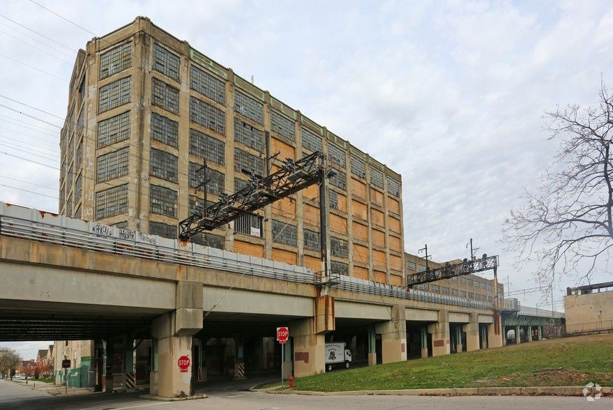A large abandoned building in Philadelphia. There is an elevated train track in front of the building. The building has many windows and an orange facade.