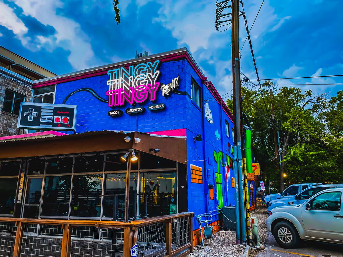 """A bright blue building with a neon sign that reads """"Tingy Tingy Tingy"""" with a patio"""
