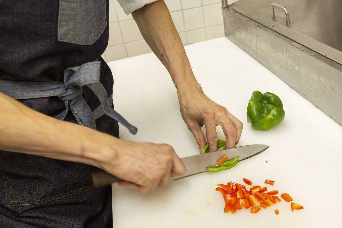 a chef chops red and green peppers