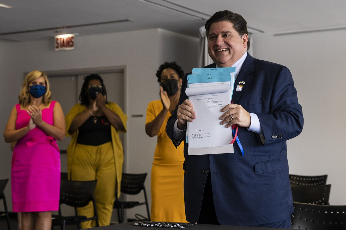 Gov. J.B. Pritzker holds up legislation aimed at advancing the rights of people in the LGBTQ community at a bill-signing ceremony on Tuesday.