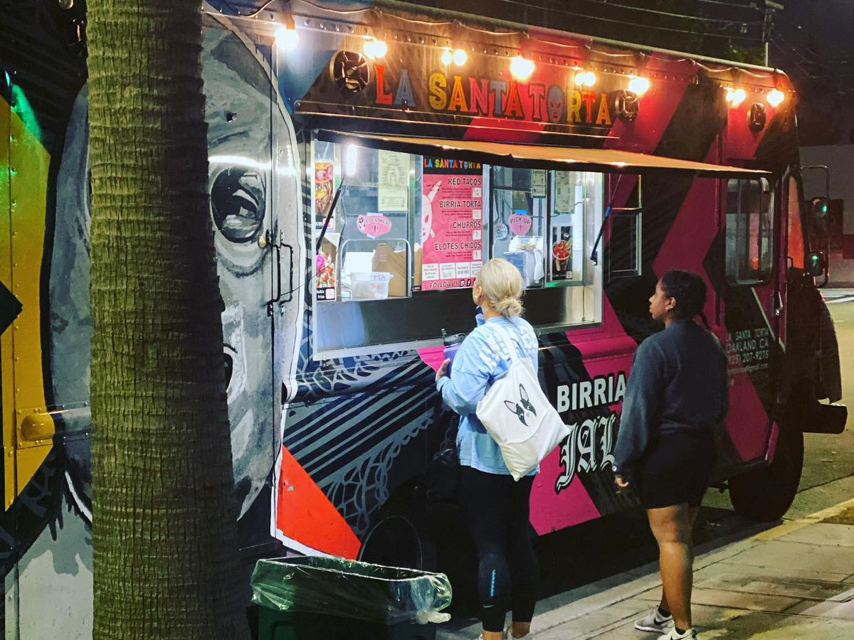 Two women stand at a brightly lit food truck decorated with a masked luchador