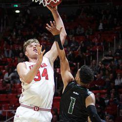 Utah Utes forward Jayce Johnson (34) shoots over Hawaii Warriors guard Drew Buggs (1) as Utah hosts Hawaii at the Huntsman Center in Salt Lake on Saturday, Dec. 2, 2017.