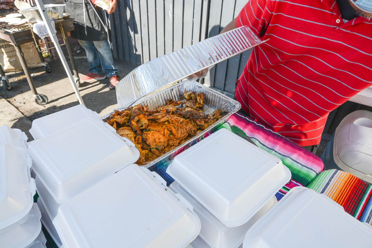 A tray of chicken ready to serve at a free food event.