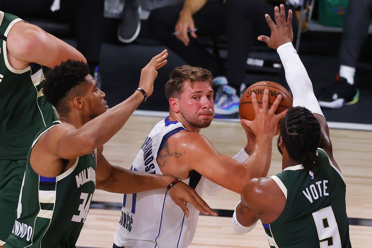 Luka Doncic of the Dallas Mavericks looks to pass around Giannis Antetokounmpo and Wesley Matthews of the Milwaukee Bucks at The Arena at ESPN Wide World Of Sports Complex on August 08, 2020 in Lake Buena Vista, Florida.