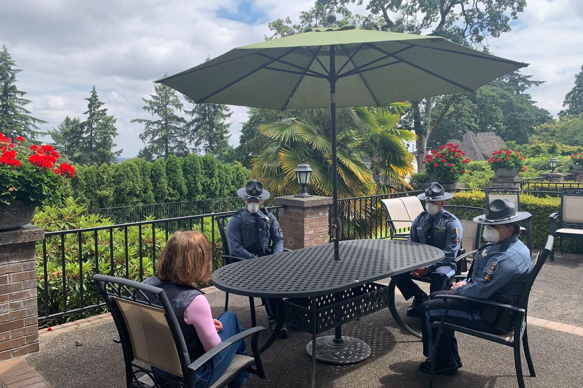 Kate Brown sits at an outdoor table with the troopers