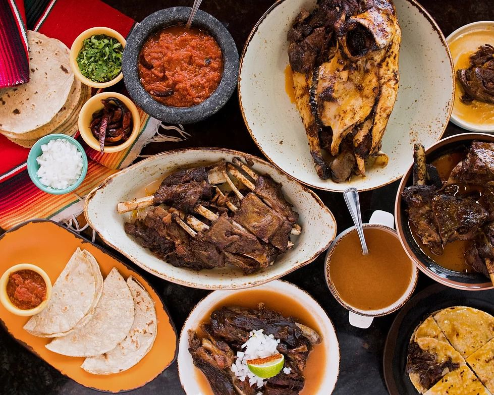 A variety of dishes laid out, including consommé, roasted goat, tortillas, and salsa.