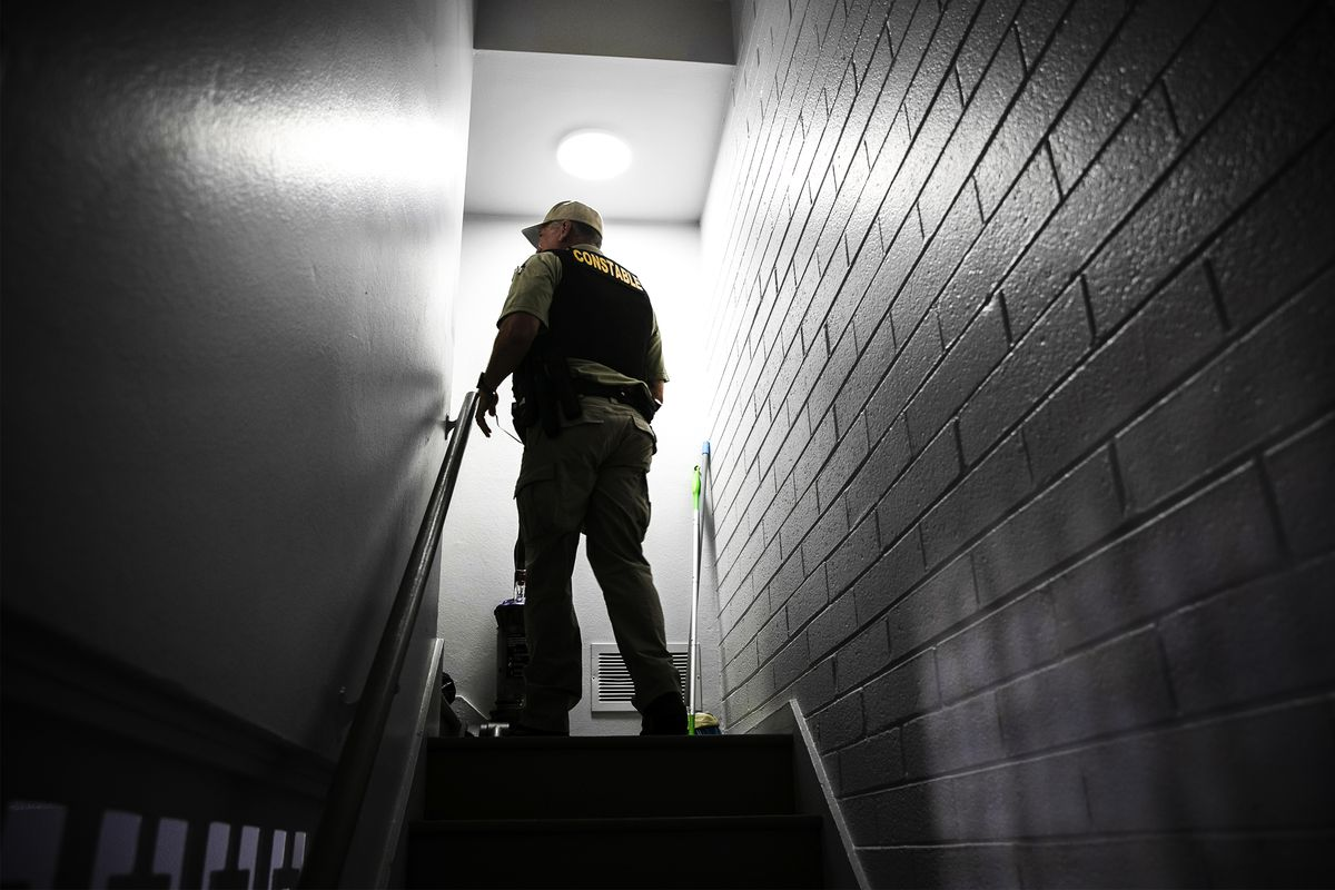 A Maricopa County constable searches as apartment while serving an eviction order on September 30, 2020, in Phoenix, Arizona.