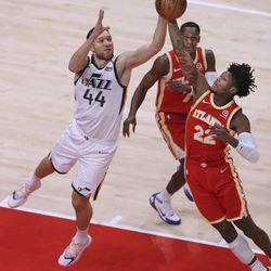 Atlanta Hawks guard Cam Reddish and Utah Jazz forward Bojan Bogdanovic reach for the ball during an NBA basketball game Thursday, Feb 4, 2021, in Atlanta.
