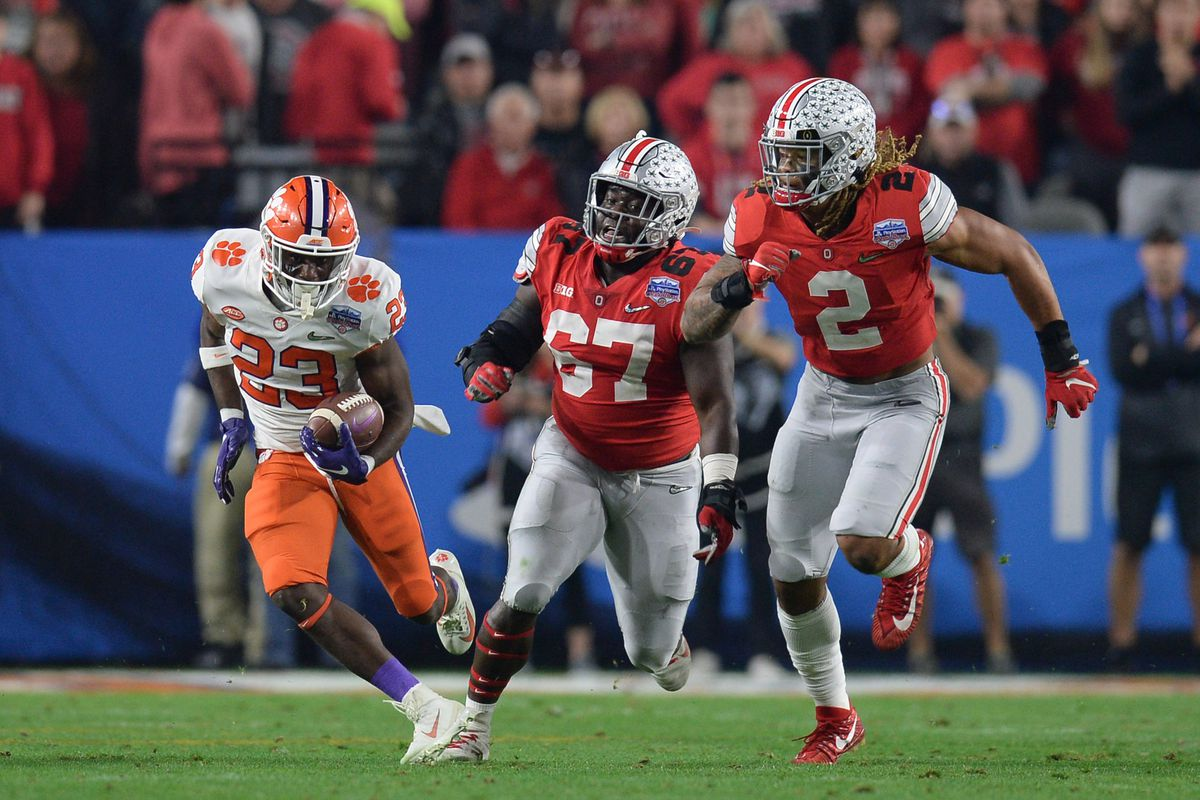 Clemson Tigers running back Lyn-J Dixon runs the ball against Ohio State Buckeyes defensive end Chase Young and defensive lineman Robert Landers during the third quarter in the 2019 Fiesta Bowl college football playoff semifinal game at State Farm Stadium.