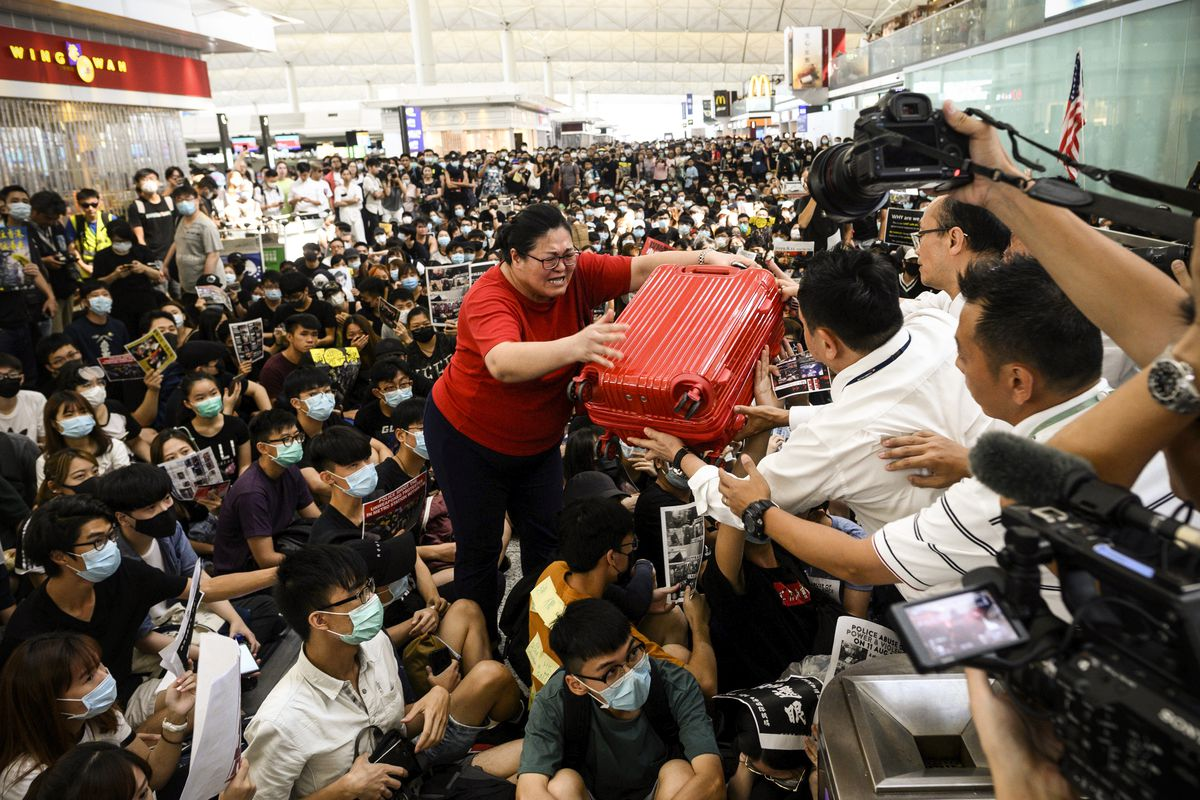 A woman hands her luggage to security guards over the heads of masked protesters sitting in the Hong Kong airport.