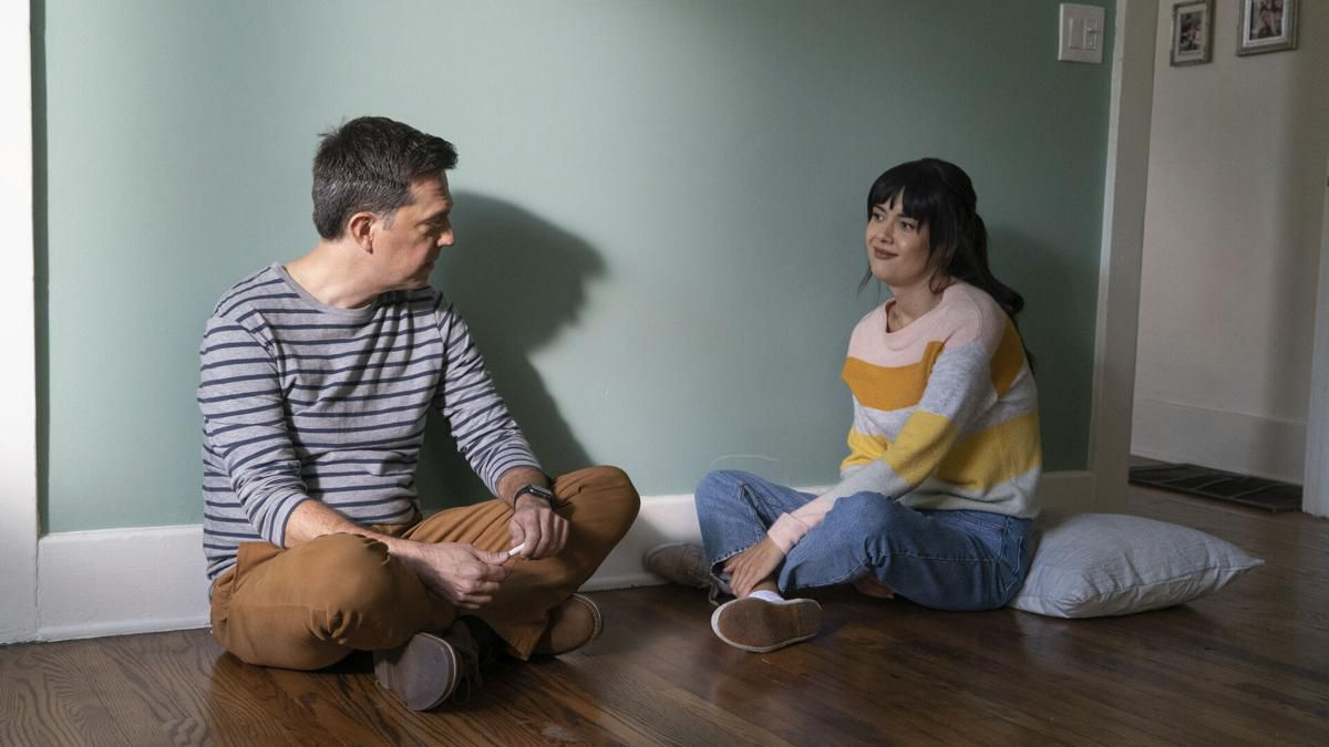 A man and a woman sit on the floor in an empty room against a greenish wall.