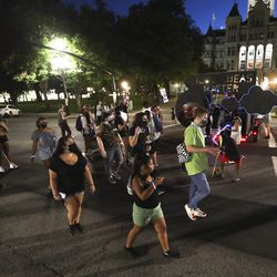 Black Lives Matter demonstrators dance to music as they walk behind a truck pulling a sound system on 200 East at the Salt Lake City-County Building on Friday, July 3, 2020.